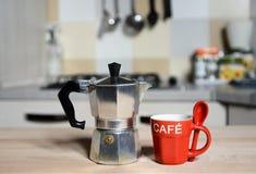 Röd kaffekopp och tappningkaffekanna på kökugnen Arkivbild