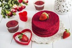Röd kaka utan röd sammet` för kräm- ` på en vit trätabell som dekoreras med för den rosor och vit openwork vasen för jordgubbar,  arkivfoton