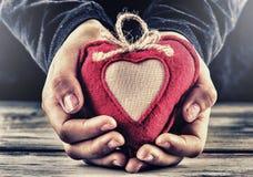 Röd kanfasvalentinhjärta i händerna av ett barn Hjärtagåva som ett tecken av förälskelse fotografering för bildbyråer