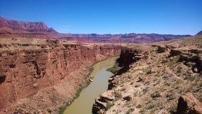 Röd kanjon med floden som flödar i mitt Fotografering för Bildbyråer