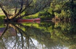 Röd kanot på flodstrand Arkivfoton