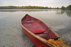 Röd kanot som sättas på land på sjön Fotografering för Bildbyråer