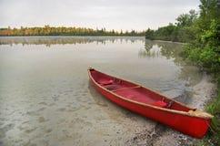 Röd kanot som sättas på land på sjön Arkivfoton
