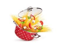 Röd kastrull med pasta och ost, grönsaker som isoleras arkivfoton