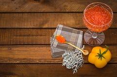 Röd kaviar i den glass kruset med guld- skedslut upp grillat hav för fiskmatparsley platta äta som är sunt banta lantligt trä för Royaltyfria Bilder