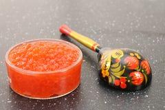 Röd kaviar i en bunke med träskeden över svart bakgrund Royaltyfri Fotografi