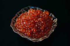Röd kaviar i glasföremål på ett svart bakgrundsslut upp n?ringsrikt begreppsmatgourmet arkivbild
