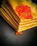 Röd kaviar på pannkakabunt på svart Royaltyfri Fotografi