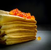 Röd kaviar på pannkakabunt på svart Royaltyfri Foto