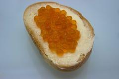 Röd kaviar på smörgåsar på den vita bakgrunden royaltyfri bild