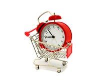 Röd klocka och shoppingvagn Arkivfoton