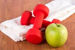 Röd konditionhantel och grönt nytt äpple med dagg på den vita handduken och trägolv Arkivfoto