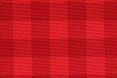 Röd kontrollerad bakgrund för sportärmlös tröjatextur Arkivfoto