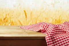 Röd kontrollerad bordduk på trädäcktabellen över bakgrund för vetefält arkivbild
