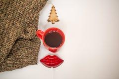 Röd kopp av den varma drinken, med julobjekt Arkivbild