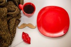 Röd kopp av den varma drinken, med julobjekt Arkivfoto