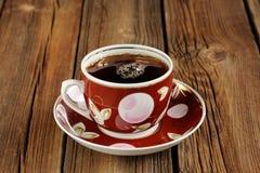 Röd kopp av svart te med bubblor på träbakgrund Arkivbild