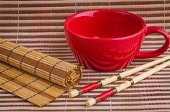 Röd kopp, bambupinnar och servett Arkivfoto