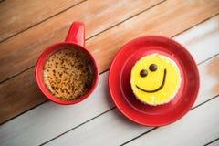 Röd kopp för kaffe och leendekaka på den wood tabellen Arkivbilder