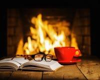 Röd kopp kaffe eller te, exponeringsglas och gammal bok på trätabell n royaltyfria bilder