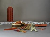 Röd kotte av tråden för att sy, blixtlås, seamripper och sax fotografering för bildbyråer