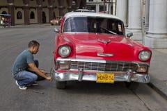 Röd kubansk bil med det plana gummihjulet från framdel Arkivbilder