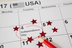 Röd kulör blyertspenna med fjärdedel av den juli kalendern Arkivfoton