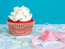 Röd kulör muffin med vaniljglasyr på kaka Royaltyfri Foto