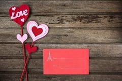 Röd kuvert- och valentingarnering med ordet FÖRÄLSKELSE på gammalt trä Arkivfoto