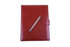 Röd läderdagbok och bollpenna som isoleras på vit Royaltyfri Foto
