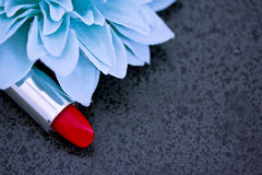 Röd läppstift och blåa blommapetals på black Arkivbild