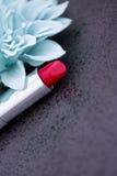 Röd läppstift och blåa blommapetals på black Royaltyfria Bilder