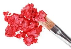 Röd läppstiftslaglängd (prövkopia) med makeupborsten fotografering för bildbyråer