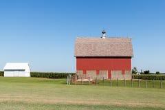 Röd ladugård i lantliga Iowa på en molnfri sommardag Arkivfoto
