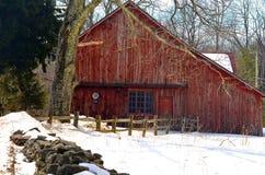 Röd ladugård i snön arkivfoton