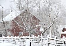 Röd ladugård i snöstorm arkivfoton