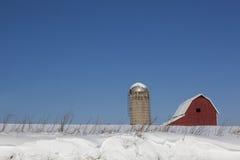 Röd ladugård i Snow arkivfoton
