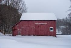 Röd ladugård i vintersnöfall royaltyfri foto