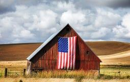Röd ladugård med amerikanska flaggan Fotografering för Bildbyråer
