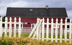 Röd ladugård med det vita posteringstaketet Arkivbild