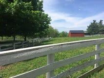 Röd ladugård med det vita staketet Fotografering för Bildbyråer