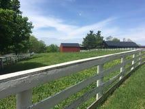 Röd ladugård med det vita staketet Arkivbilder