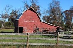 Röd ladugård med ett ridit ut staket royaltyfria bilder