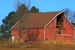 Röd ladugård med saknad för hövinddörr royaltyfri bild