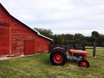 Röd ladugård och traktor Arkivbilder