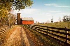 Röd ladugård på slutet av grusvägen Royaltyfria Bilder