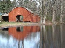 Röd ladugård vid sjön Royaltyfri Foto