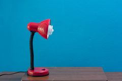 Röd lampa på det Wood skrivbordet för tappning på blå väggbakgrund Arkivbilder