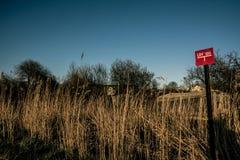 Röd landgranskningsfläck i fältet royaltyfri fotografi