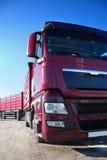 Röd lastbil med släpet Arkivbild